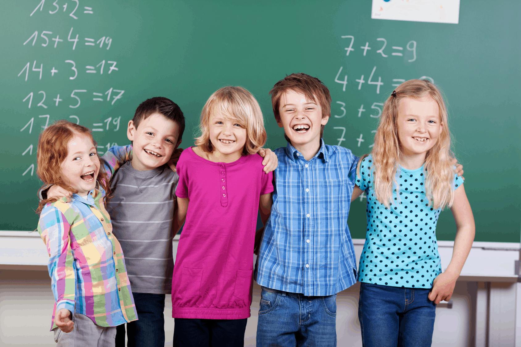 Kinder stehen lachend vor Tafel
