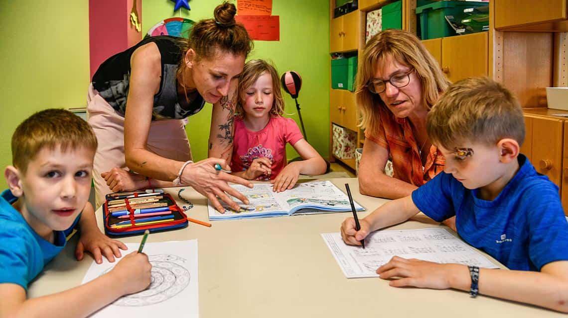 Erzieherin und Schulleiterin helfen Kindern bei den Hausaufgaben