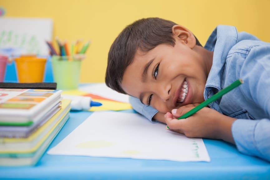 Junge mit Stift über Papier gebeugt