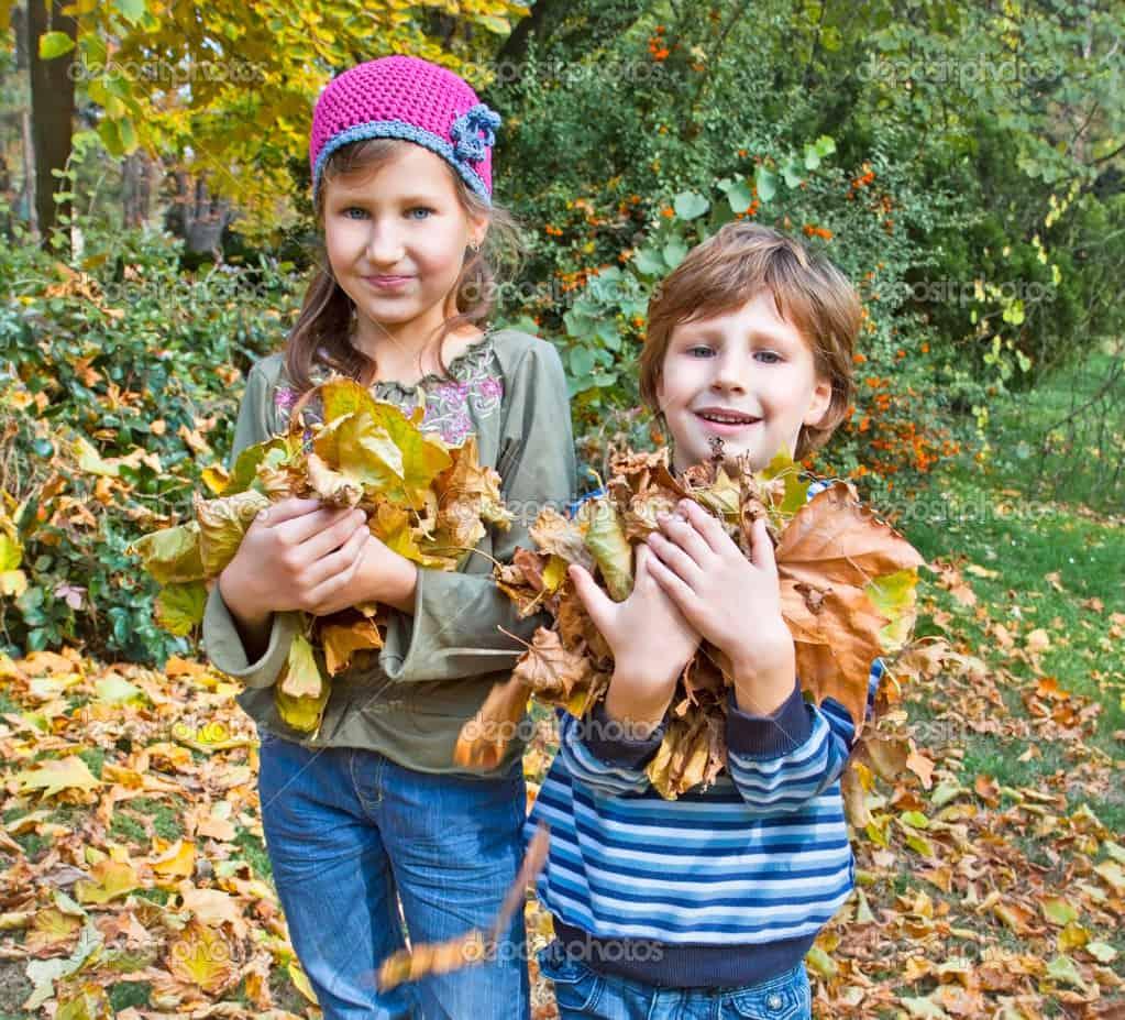 Kinder spielen im Herbst mit Laub