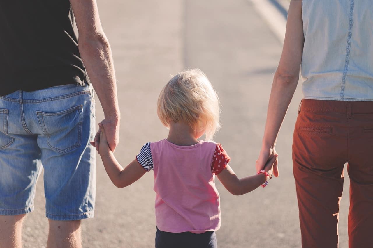 Eltern halten Kind an der Hand