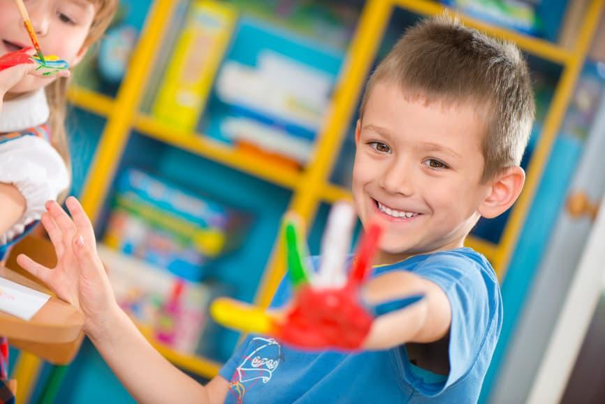 Kind mit bemalter Hand im Kindergarten