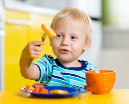 Kleinkind isst mit einer Gabel