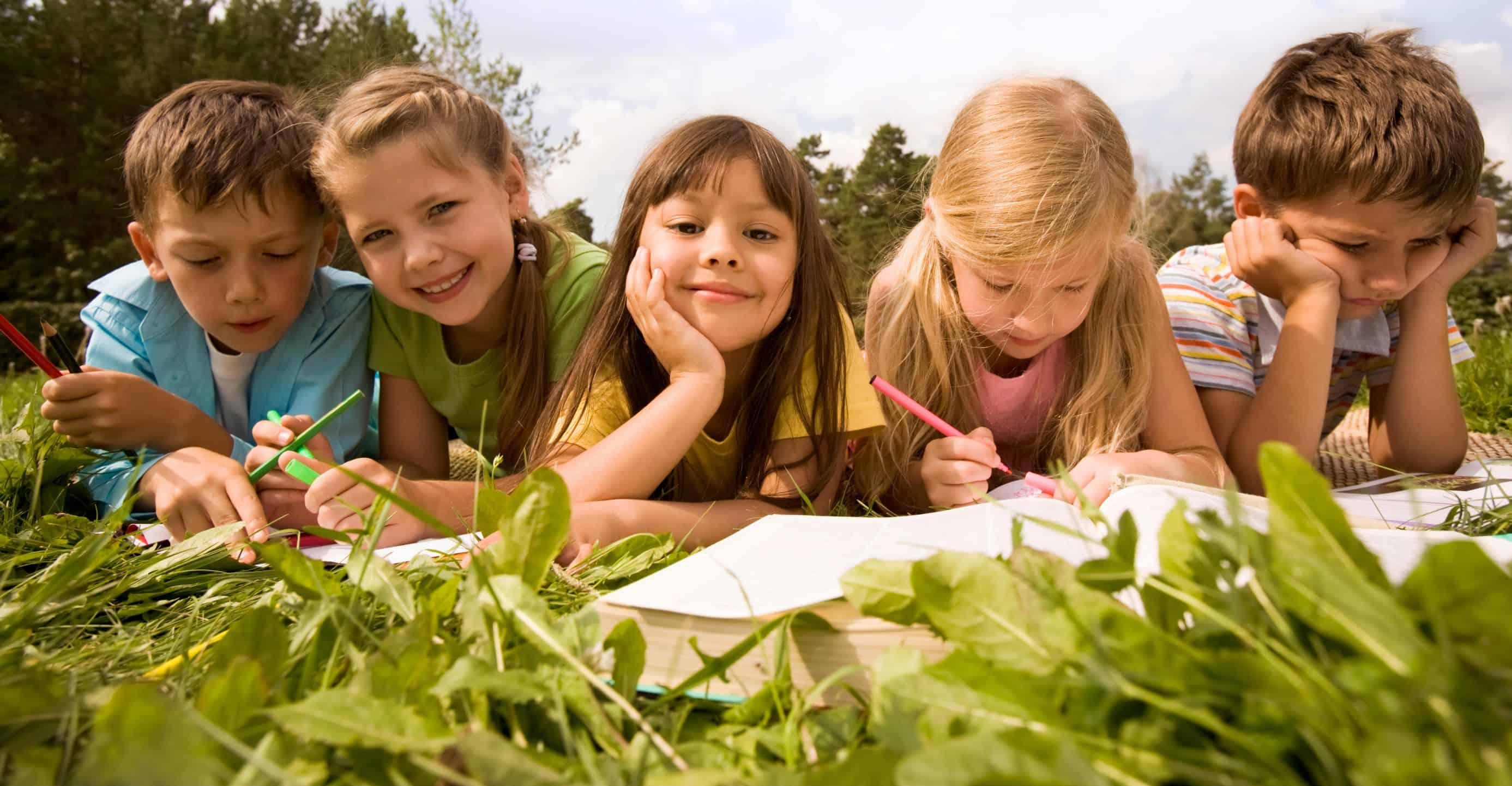 Hortkinder liegen auf der Wiese und lernen