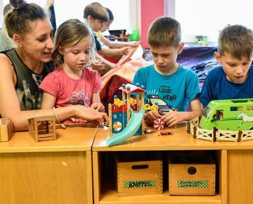 Hortkinder spielen Playmobil mit Erzieherin