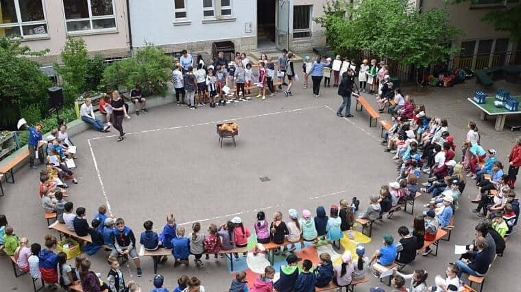 Kinder sitzen auf Bänken um das Pfingstfeuer