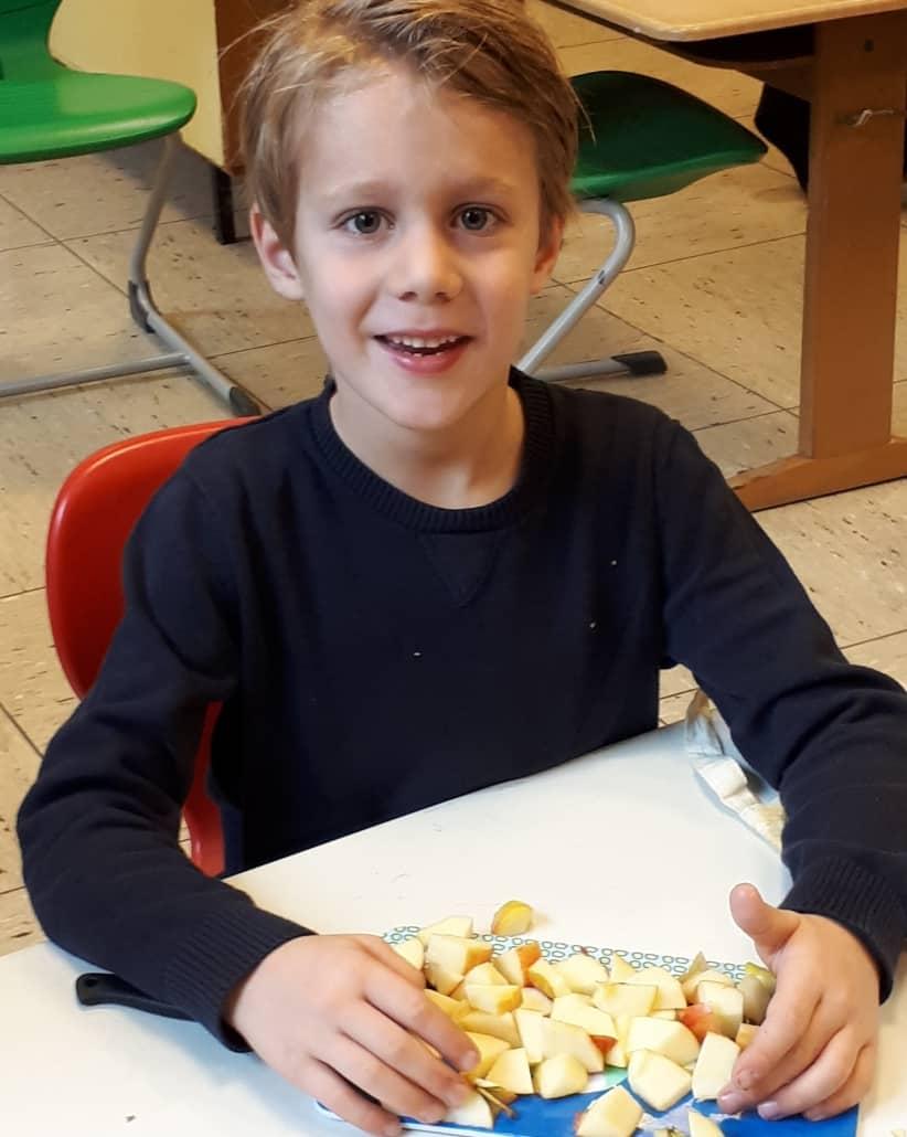 Junge schneidet Äpfel für Apfelbrei